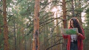 Турист молодой женщины с рюкзаком и биноклями идет через древесину после этого стоя и смотря карта выбирая путь видеоматериал