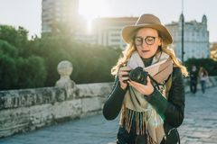 Турист молодой женщины, фотограф, девушка битника в шляпе стоит на улице города и использует камеру, взгляды отображает на экране Стоковые Фото