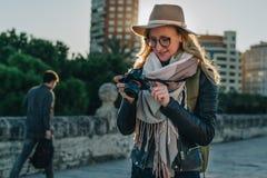 Турист молодой женщины, фотограф, девушка битника в шляпе стоит на улице города и использует камеру, взгляды отображает на экране Стоковые Фотографии RF