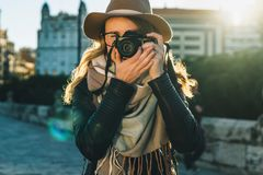 Турист молодой женщины, фотограф, девушка битника одел в шляпе и eyeglasses, стойках на улице города и принимает фото Стоковое Изображение RF