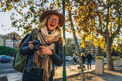 Турист молодой женщины, фотограф, девушка битника сидит на стенде на улице города и принимает фото Каникулы, перемещение, приключ Стоковые Изображения
