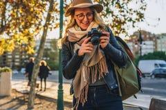 Турист молодой женщины, фотограф, девушка битника сидит на стенде на улице города и принимает фото Каникулы, перемещение, приключ Стоковое Фото