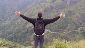 Турист молодого человека при рюкзак стоя на краю красивого каньона и победоносно поднятых рук Мыжской hiker сток-видео