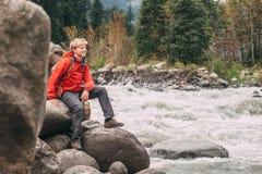 Турист молодого человека сидит речной берег скалистой горы Стоковая Фотография