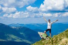 Турист молодой женщины на крае ` s скалы гор поднимает вверх руку с наслаждается и счастье Красивый вид неба на верхней горе Стоковая Фотография