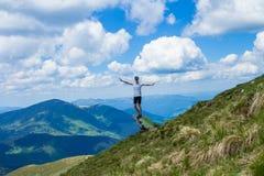 Турист молодой женщины на крае ` s скалы гор поднимает вверх руку с наслаждается и счастье Красивый вид неба на верхней горе Стоковое Изображение RF