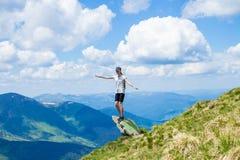 Турист молодой женщины на крае ` s скалы гор поднимает вверх руку с наслаждается и счастье Красивый вид неба на верхней горе Стоковое фото RF