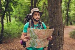 Турист мужского брюнет бородатый confused выпаданный из ускорения в лесе, держащ карту, смотрящ далеко, пробуя находить Он имеет  Стоковая Фотография RF