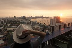 Турист наблюдает красивый заход солнца на крыше гостиницы для Паттайя стоковая фотография rf