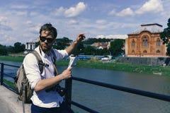 Турист на улице держит гида или карты и пунктов на здании Путешественник на речном береге пробуя найти путь Стоковые Фото