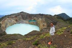 Турист на Kelimutu наблюдая уникально кран и олово озер Стоковые Изображения