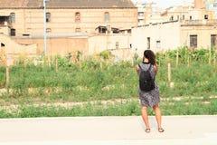 Турист принимая фото сада и домов в Барселоне Стоковые Изображения RF