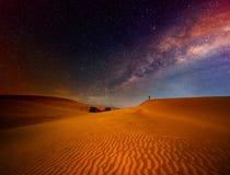Турист при рюкзак стоя на верхней части и наслаждаясь ночным небом Стоковое фото RF
