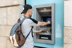 Турист разделяет деньги от ATM для более дальнеишего перемещения Финансы, кредитная карточка, разведение денег стоковое фото rf