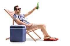 Турист сидя в шезлонге и провозглашать с пивом Стоковое Фото