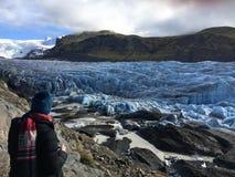 Турист смотря ледник Svinafellsjokull в Исландии отступая стоковые фото