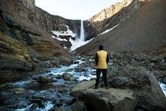 Турист стоит с его задняя часть смотря водопад стоковая фотография rf