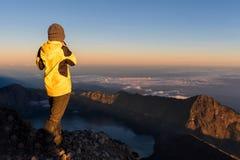 Турист стоя na górze горы Rinjani и наслаждается взглядом восхода солнца вулкана Стоковое Изображение RF
