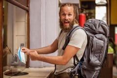 Турист счастливого и эйфоричного backpacker мужской показывает билет для его стоковые фотографии rf