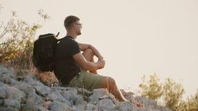 Турист с большим рюкзаком сидит на утесах и отдыхает на заходе солнца видеоматериал