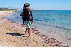 Турист с большим рюкзаком идя через чистую воду Средиземного моря Стоковое Изображение