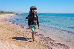 Турист с большим рюкзаком идя через чистую воду Средиземного моря Стоковая Фотография RF