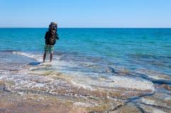Турист с большим рюкзаком идя через чистую воду Средиземного моря Стоковые Фотографии RF