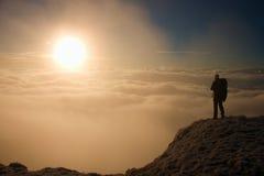 Турист с большим рюкзаком стоит на точке зрения и наблюдает в туманную долину зима утра солнечная Стоковое Изображение