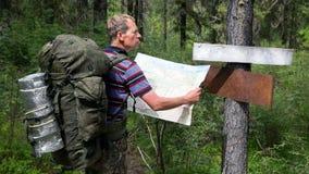 Турист с картой около указателей, местом для текста стоковое изображение