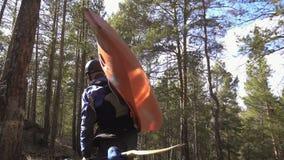 Турист с каяком на его задние движения к реке горы через туриста перемещения образа жизни соснового леса видеоматериал