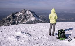 Турист с рюкзаком и поляками смотря на горах зимы стоковые фото