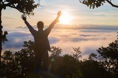 Турист с рюкзаком на наклоне горы с поднятыми руками сверх, стоковые фото