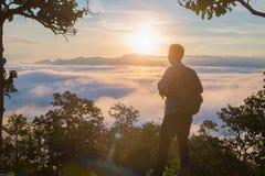 Турист с рюкзаком на наклоне горы с поднятыми руками сверх, стоковые фотографии rf