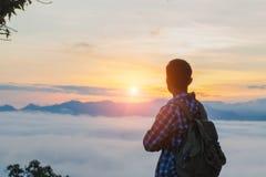 Турист с рюкзаком на наклоне горы с поднятыми руками сверх, стоковая фотография rf
