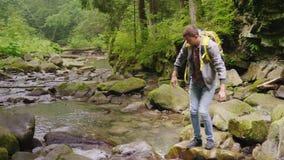 Турист с рюкзаком пересекает реку горы над утесами Опасный момент - почти падения, выскальзывания опасно акции видеоматериалы