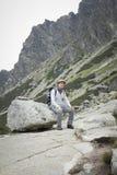 Турист с рюкзаком сидя на валуне в горах стоковая фотография rf