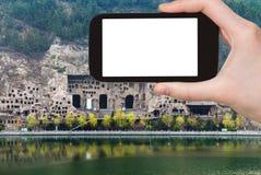 турист фотографирует гроты Longmen в Китае Стоковая Фотография