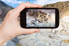турист фотографирует кислотное mudpot в Исландии стоковое изображение