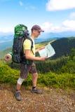 Турист человека в горе прочитал карту Стоковые Изображения