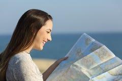Турист читая карту на пляже Стоковое Фото