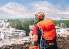 Турист Backpacker смотрит на голубой горе Стоковая Фотография RF