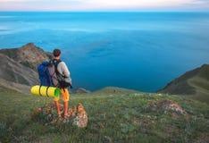 Турист na górze горы наслаждаясь видом на море Стоковые Фотографии RF