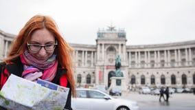Турист Yong - женщина при красные волосы и стекла смотря карту в Heldenplatz, вене Стоковое Изображение