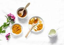 Турмерин, мед, лицевой щиток гермошлема молока кокоса Домодельные продукты красоты ингридиентов на светлой предпосылке, взгляд св стоковое фото