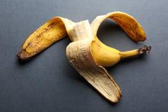 Тухлый сдержанный банан на серой предпосылке Стоковая Фотография RF