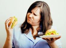 Тучная белая женщина имея выбор между гамбургером и салатом, есть эмоциональную нездоровую еду, концепция людей образа жизни стоковые изображения