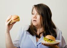 Тучная белая женщина имея выбор между гамбургером и салатом Стоковое фото RF