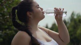 Тучная девушка выпивает воду от бутылки сток-видео