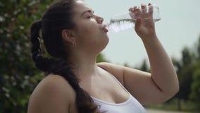 Тучная девушка выпивает воду от бутылки акции видеоматериалы