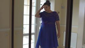 Тучная девушка в голубом платье перед зеркалом сток-видео